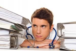 Ein Arzt im Stress mit Akten Stapel. Bürokratie im Krankenhaus.